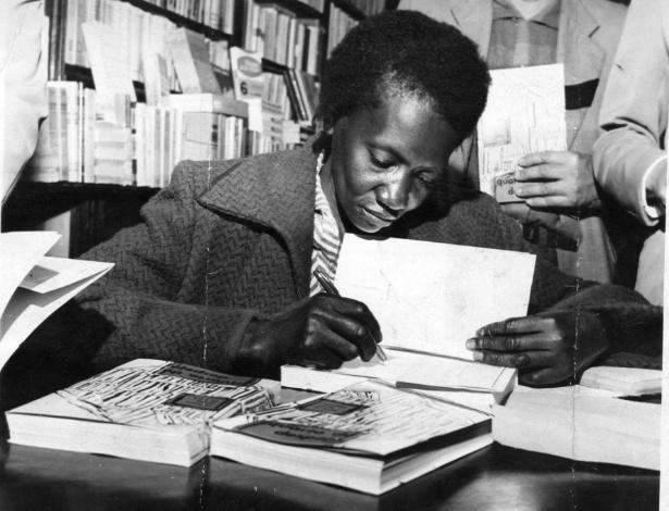 """A escritora brasileira Carolina Maria de Jesus durante noite de autógrafos do lançamento de seu livro """"Quarto de Despejo"""", em uma livraria na rua Marconi, em São Paulo (SP), no ano de 1960"""