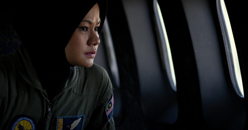 15.mar.2014 - Membro da tripulação de buscas da Força Aérea da Malásia olha pela janela de avião que trabalha na busca do avião da companhia Malaysia Airlines, desaparecido desde o dia 8 de março