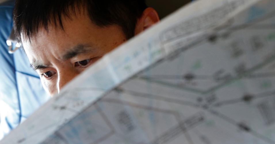 15.mar.2014 - Um oficial da Guarda Costeira do Japão estuda um mapa de bordo de suas aeronaves Gulfstream V Jet, personalizado para operações de busca e salvamento, já que procurar os desaparecidos avião Malaysia Airlines MH370 sobre as águas do Mar da China Meridional. Os investigadores acreditam que alguém a bordo desligou deliberadamente o sistema de comunicação