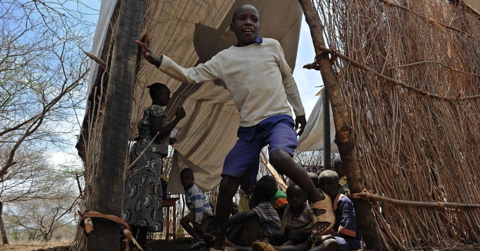 17.mar.2014 - Estudante sai da sala de aula em uma aldeia no Quênia. A lona do telhado foi arrancada depois de fortes chuvas na região da aldeia de Chesesoi