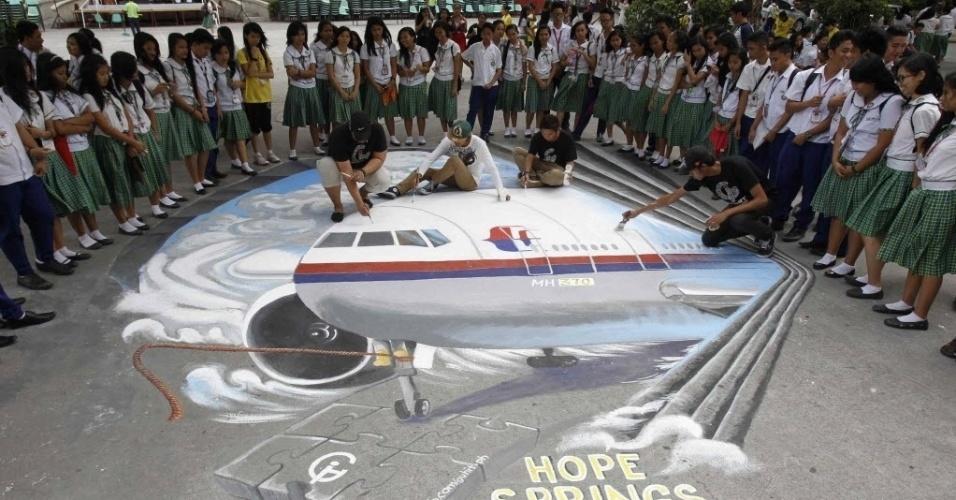 17.mar.2014 - Estudantes observam grupo de artistas fazendo retoques em desenho em homenagem ao voo MH370 da Malaysia Airlines, em escola na cidade de Makati, próximo a Manila, nas Filipinas
