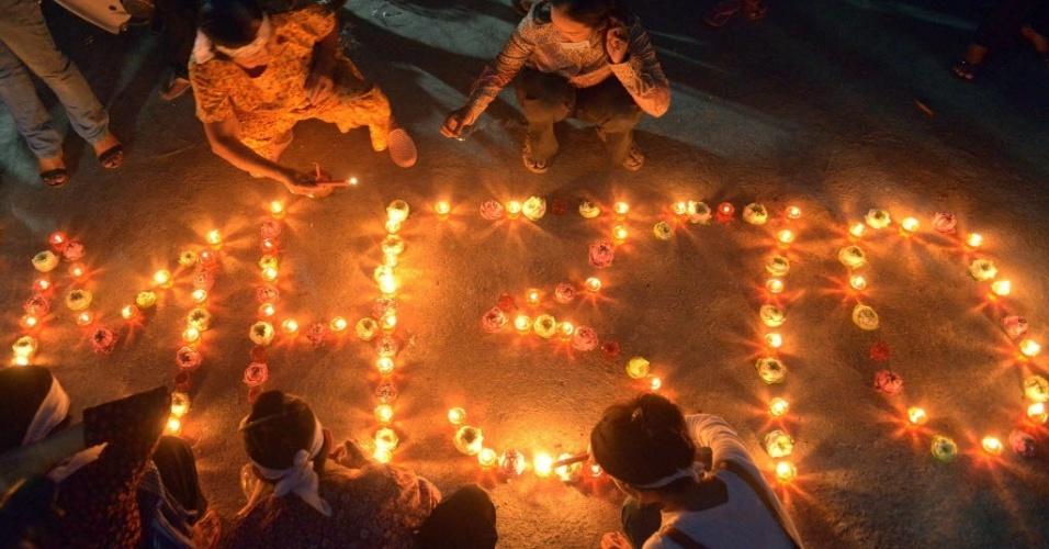 17.mar.2014 - Moradores de vila em Phnom Penh, no Camboja, acendem velas em homenagem aos passageiros do voo MH370 da Malaysia Airlines, que está desaparecido desde 8 de março