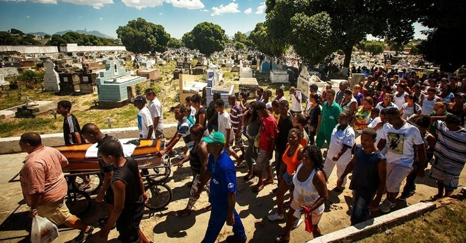 17.mar.2014 - Parentes e amigos se reúnem no cemitério do Irajá, na zona norte do Rio de Janeiro, para o sepultamento de Claudia Silva Ferreira, 38, nesta segunda-feira (17). A moradora do morro da Congonha, em Madureira, foi encontrada baleada pelos policiais no alto da favela, depois de um tiroteio. Dois subtenentes e um soldado do batalhão da PM de Rocha Miranda resolveram colocá-la no porta-malas do carro da polícia. No trajeto para o hospital, o porta-malas se abriu e ela foi projetada para fora do carro, sendo arrastada pelo veículo