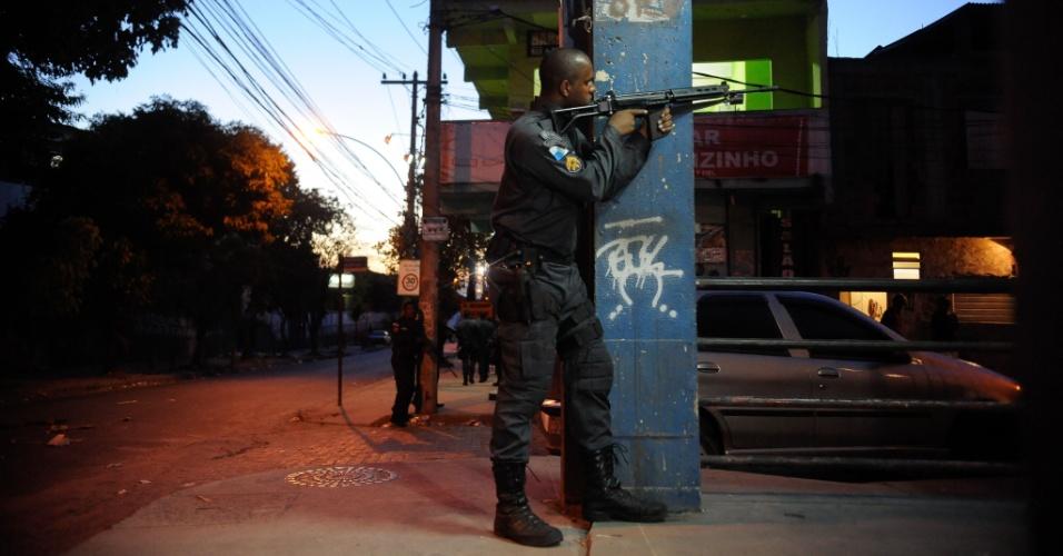 17.mar.2014 - Policial aponta arma durante protesto contra a morte de Cláudia Ferreira da Silva, 38, no morro da Congonha, em Madureira, na zona norte do Rio de Janeiro. A mulher foi arrastada por uma viatura da Polícia Militar após ser baleada durante tiroteio entre a polícia e criminosos na comunidade no domingo (16)