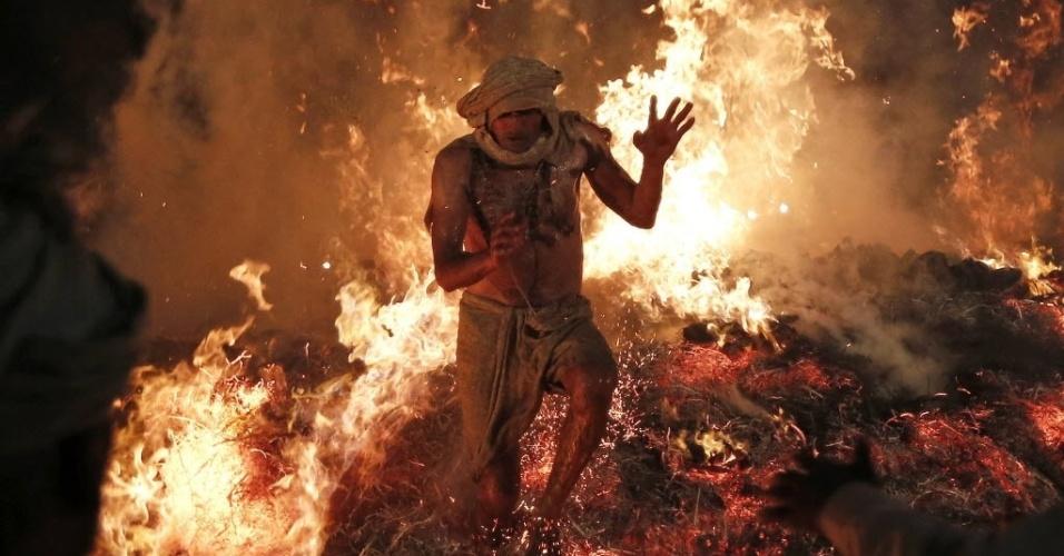 17.mar.2014 - Sacerdote hindu salta fogueira que simboliza a queima do demônio Holika durante um ritual para marcar o primeiro dia do festival de primavera Holi, conhecido como festival das cores, na aldeia de Phalen, Índia