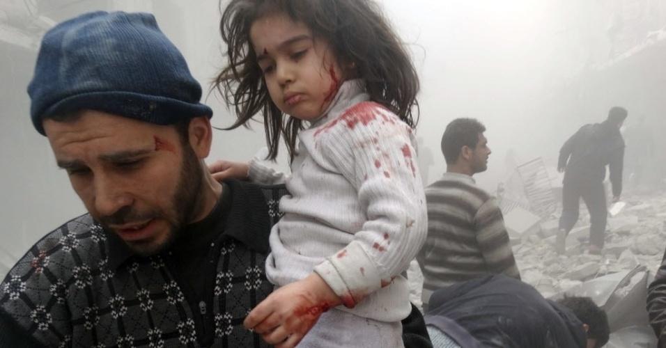 18.mar.2014 - Homem retira criança de local de explosão causada por forças governamentais em Aleppo, na Síria, nesta terça-feira (18)