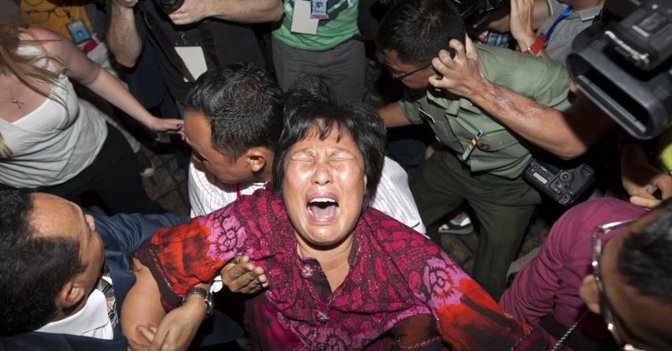 19.mar.2014 - Familiar de passageiro do MH370 , da Malaysian Airlines, que desapareceu no dia 8 de março, chora em frente a jornalistas na sala de imprensa do aeroporto de Kuala Lumpur. Vários familiares de passageiros chineses que estavam a bordo do avião desaparecido  invadiram a sala onde autoridades malaias faziam um pronunciamento a jornalistas