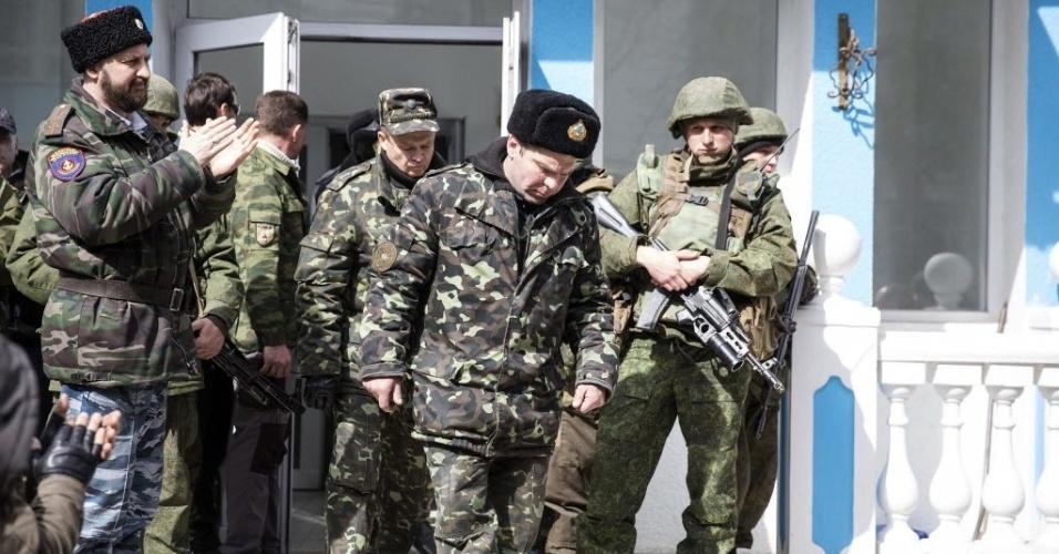 19.mar.2014 - Militares ucranianos deixam sede naval em Sebastopol vigiados por soldados russos. Milícias pró-Rússia desalojaram a sede da Marinha ucraniana no porto de Sebastopol, um dia depois da incorporação da península da Crimeia à Rússia