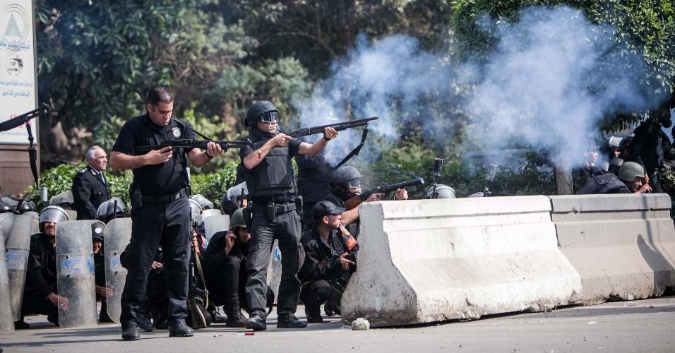 19.mar.2014 - Policiais atiram bombas de gás lacrimogêneo para dispersar manifestantes, próximo a Universidade do Cairo, nesta quarta-feira (19). Múltiplos confrontos ocorreram nesta quarta entre apoiadores do presidente deposto Mohammed Mursi e policiais por todo o país, um deles resultou na morte de um adolescente, na província de Beni Sweif