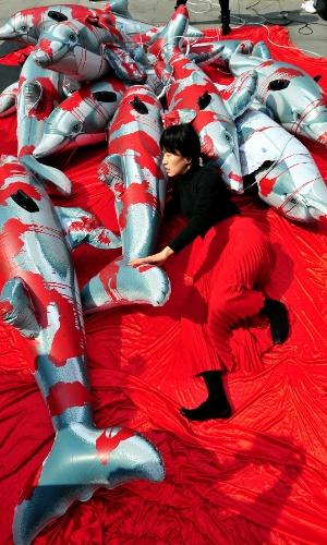 20.mar.2014 - Ativista ambiental sul-coreana deita com golfinhos de plástico durante ação contra a caça cruel de golfinhos, nesta quinta-feira (20), em Seul. Os ativistas pedem que aquários da Coreia do Sul deixem de importar golfinhos do Japão, onde pescadores insistem em empregar métodos brutais para caçar os cetáceos, sobretudo na baía de Taiji, que já foi tema do documentário vencedor do Oscar 'The Cove'