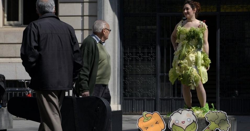 20.mar.2014 - Ativista usa vestido feito com folhas de alface para protestar contra o consumo de carne, no centro de Barcelona, na Espanha
