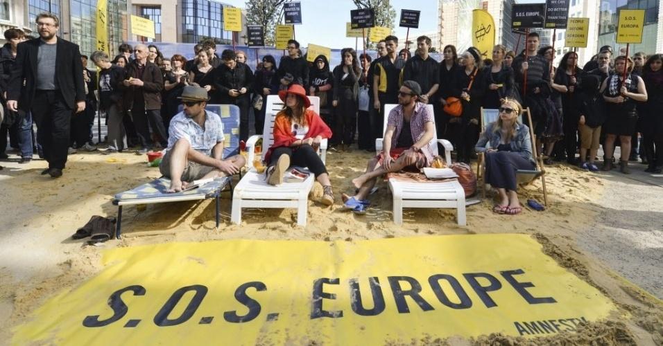 20.mar.2014 - Ativistas a favor dos direitos humanos fazem protesto em frente à sede da União Europeia, em Bruxelas (Bélgica), pedindo respeito aos direitos dos imigrantes e refugiados