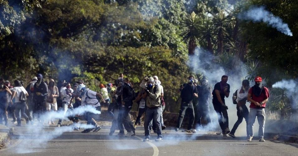 20.mar.2014 - Ativistas anti-governo entram em confronto com a Polícia Nacional, que joga bombas de gás lacrimogêneo, durante um protesto contra o presidente venezuelano, Nicolás Maduro, em Caracas, na Venezuela