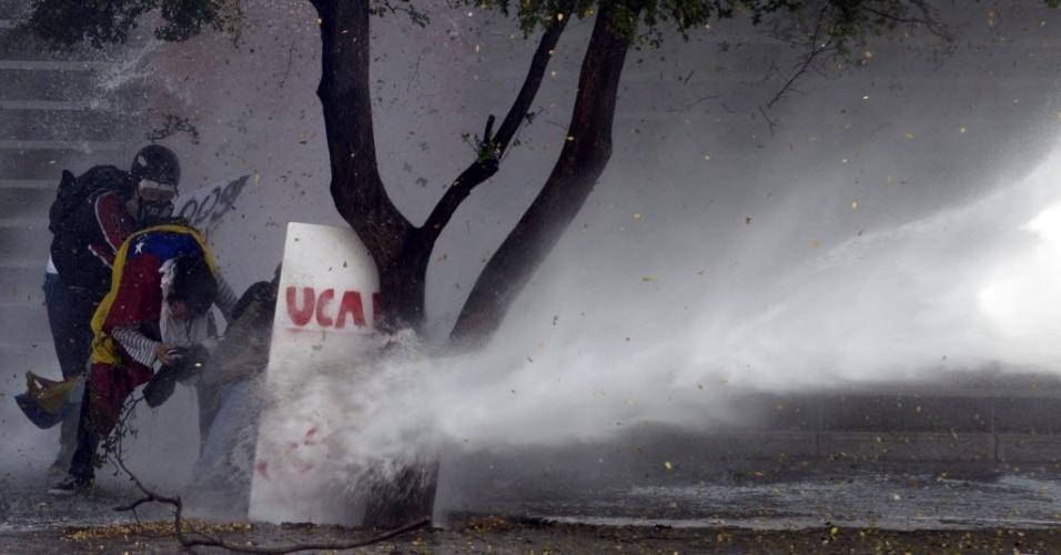 20.mar.2014 - Ativistas anti-governo protestam contra o presidente venezuelano, Nicolás Maduro, e se escondem atrás de uma árvore enquanto a Polícia Nacional joga água para espalhar os manifestantes, em Caracas