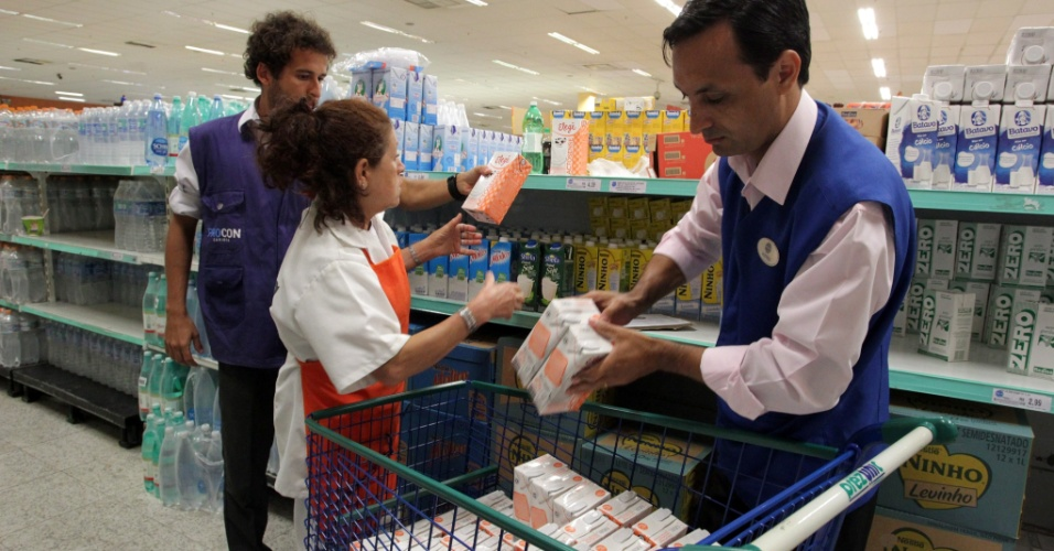 20.mar.2014 - Funcionários do Procon (Fundação de Proteção e Defesa do Consumidor) retiram leite da marca Elegê das prateleiras de um supermercado de Botafogo, no Rio de Janeiro
