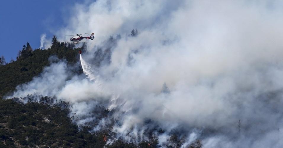 20.mar.2014 - Helicóptero joga água em incêndio na montanha de Runstboden, na vila de Absam, na Áustria