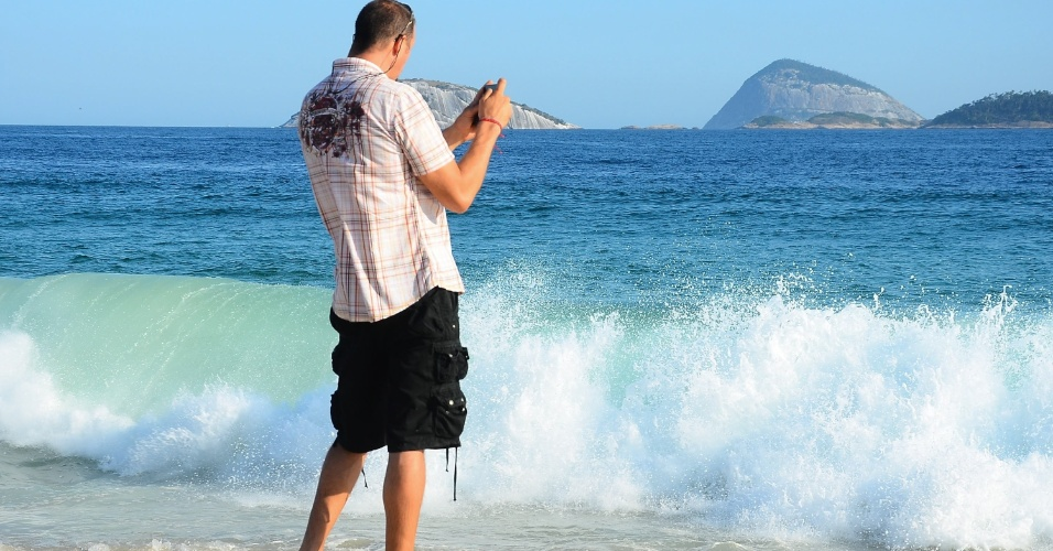 20.mar.2014 - Homem fotografa o mar na praia de Ipanema durante a primeira tarde de outono do ano, com o mar com princípio de ressaca, sol, calor e nuvens