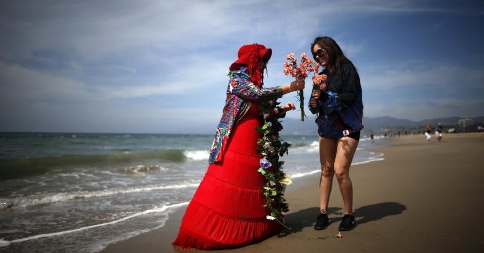 20.mar.2014 - Mulher distribui cravos na praia para celebrar o primeiro dia da primavera, em Santa Monica, na Califórnia, nos Estados Unidos
