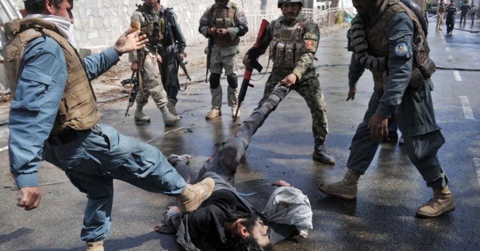 20.mar.2014 - Policiais chutam corpo de membro do Taleban que participou de ataque a uma delegacia na cidade de Jalalabad, nesta quinta-feira (20).