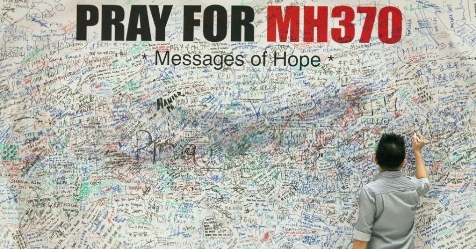 22.mar.2014 - Visitante escreve mensagem de esperança para os passageiros e tripulantes do voo MH370, da Malaysia Airlines, neste sábado (22), em Kuala Lumpur, Malásia. O avião está desaparecido há duas semanas. A China detectou objetos que podem  estar relacionados ao desaparecimento da aeronave