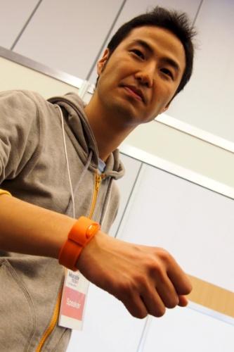 26.mar.2014 - Akinori Takahagi, fundador da Moff, veste a pulseira inteligente que leva o mesmo nome de sua companhia. Equipado com sensores, o gadget transforma qualquer atividade em brincadeira. Dependendo do movimento que o usuário faz, ele emite um som que pode ser escolhido por meio de um aplicativo móvel. É possível, por exemplo, escolher o som de piano. A cada movimento realizado, a pulseira emite o som do instrumento