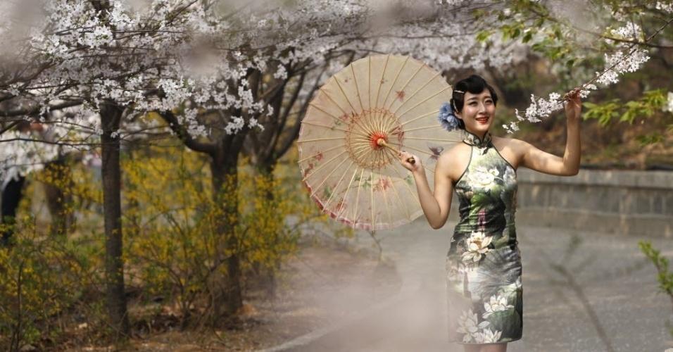 26.mar.2014 - Modelo posa com flores de cerejeira em montanha de Zouping, na China. Turistas de todo o país visitam o local para observar a paisagem