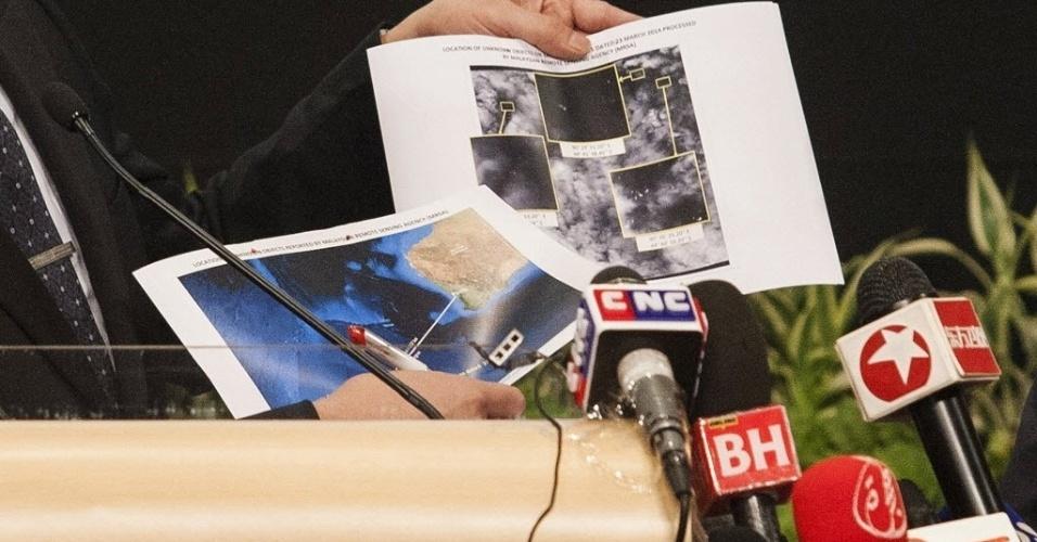 26.mar.2014 - O ministro da Defesa da Malásia, Hishamuddin Hussein, mostra novas fotografias do que podem ser os restos do avião desaparecido. Imagens de satélite revelam a presença de 122 objetos flutuando em uma zona de 400 quilômetros quadrados em uma das áreas de busca do sul do oceano Índico, onde o voo MH370 pode ter caído