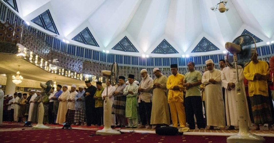 27.mar.2014 - Grupo de muçulmanos reza por pessoas a bordo do voo MH370 da Malaysia Airlines, em mesquita em Kuala Lumpur, na Malásia