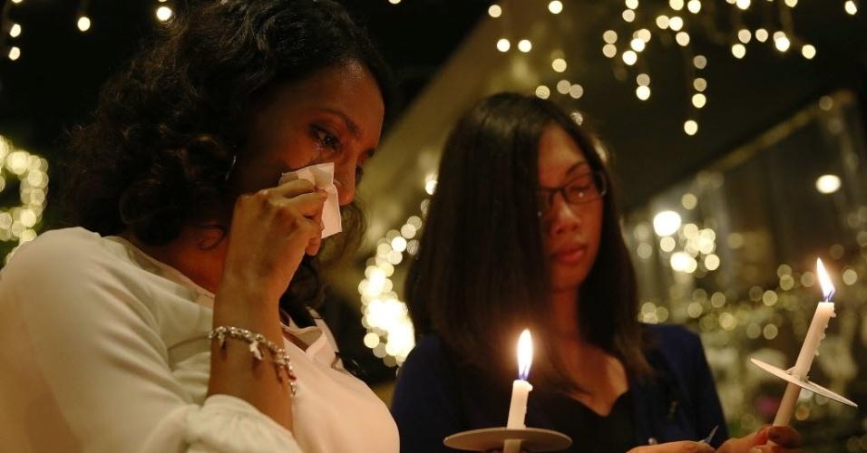 27.mar.2014 - Mulher enxuga lágrima durante ato em memórias aos passageiros e tripulantes do voo MH370 da Malaysia Airlines, em frente a um centro comercial em Kuala Lumpur, na Malásia, nesta quinta-feira (27)