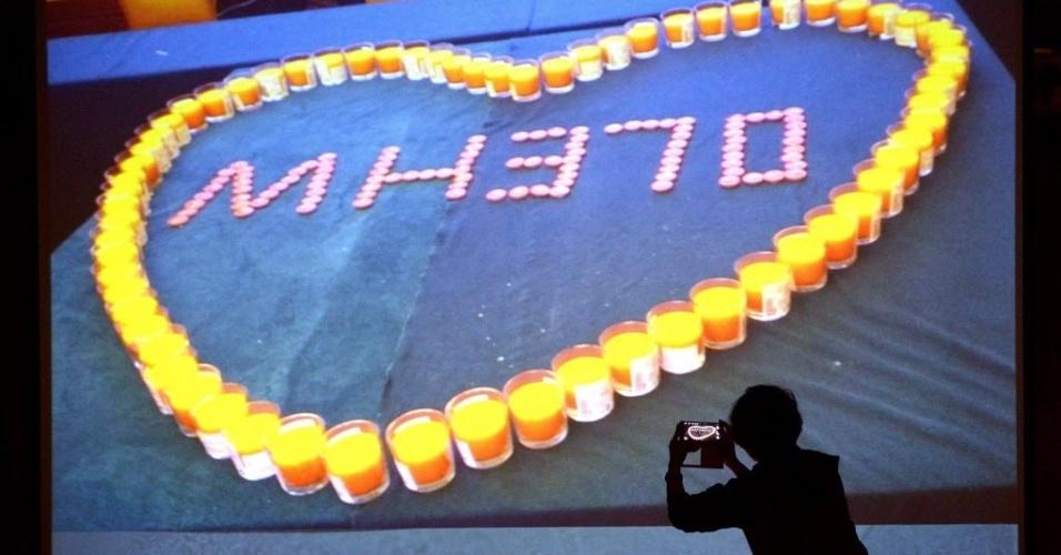 27.mar.2014 - Mulher tira foto de tela que mostra homenagem aos passageiros e tripulantes do voo MH370 da Malaysia Airlines, em Pequim, na China