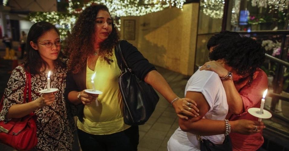 27.mar.2014 - Mulheres se abraçam enquanto seguram velas durante ato em memórias aos passageiros e tripulantes do voo MH370 da Malaysia Airlines, em frente a um centro comercial em Kuala Lumpur, na Malásia, nesta quinta-feira (27)