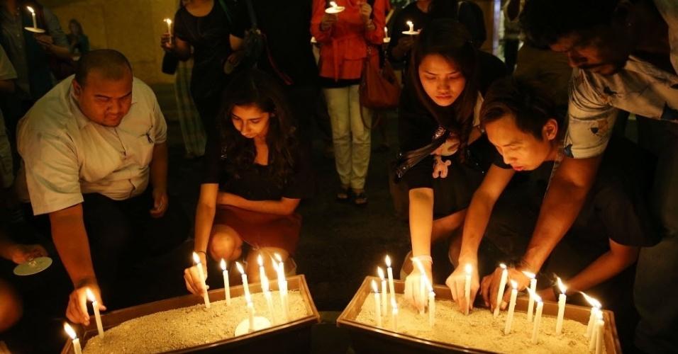 27.mar.2014 - Velas são acesas em memórias aos passageiros e tripulantes do voo MH370 da Malaysia Airlines, em frente a um centro comercial em Kuala Lumpur, na Malásia, nesta quinta-feira (27)