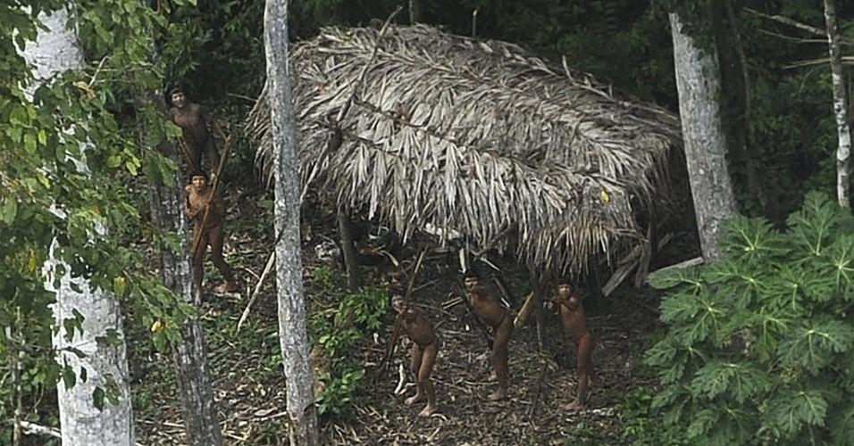 28.mar.2014 - Indígenas observam avião que sobrevoa seu território que fica na bacia do Amazonas, próximo ao rio Xinane, no Estado do Acre, vizinho à fronteira com o Peru, em foto tirada no dia 25 de março pela agência Reuters e divulgada nesta sexta-feira (28). Antropólogos acreditam que a comunidade viva isolada do restante da civilização. Líderes da tribo ashaninka, que compartilha o território com esses índios isolados e outras tribos, pediram ajuda ao governo e organizações não governamentais para controlar o que eles consideram a invasão dessas tribos em sua própria área, afirmando que o movimento de outras tribos é causado pela pressão da exploração madeireira ilegal na fronteira com o Peru