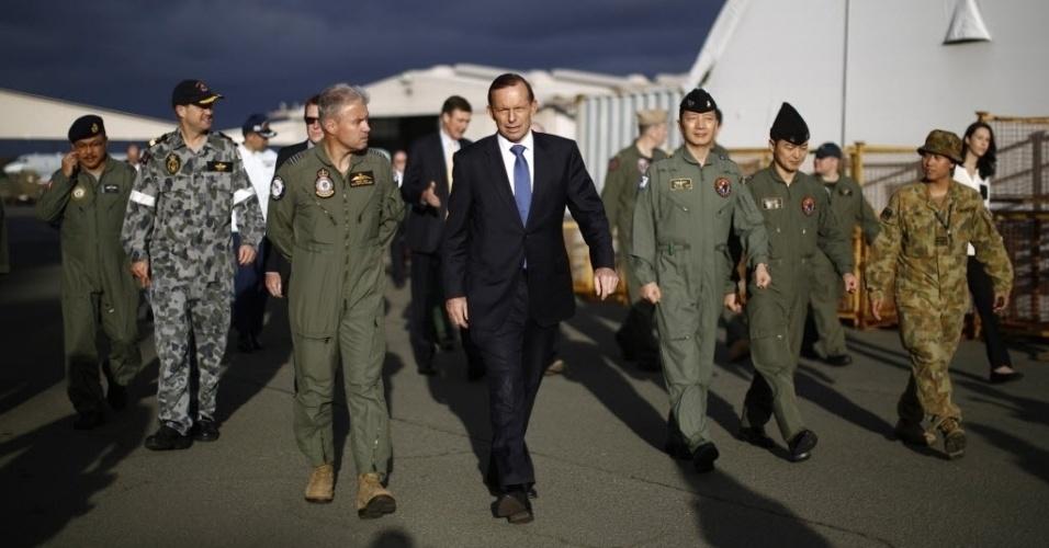 30.mar.2014 - O primeiro-ministro da Austrália, Tony Abbott, anda ao lado do comandante da Força Aérea australiana, Craig Heap (terceiro à esquerda), durante visita de Abbott a base aérea de Pearce, perto de Perth (Austrália), nesta segunda-feira (31). O governo australiano coordena às buscas pelo avião da Malaysia Airlines que desapareceu no começo do mês