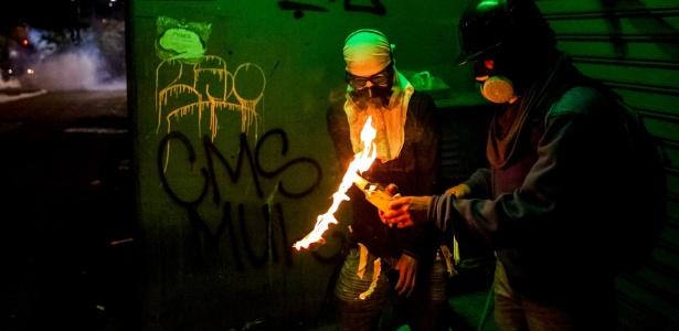 Manifestantes preparam coquetel molotov durante enfrentamento com a polícia venezuelana em Caracas. O presidente venezuelano disse neste domingo (30) que está aberto para suavizar a força contra a oposição se ela aceitar sentar-se à mesa para negociar um fim aos protestos. Duas pessoas morreram neste domingo; em quase dois meses de protesto, houve um total de 39 mortes