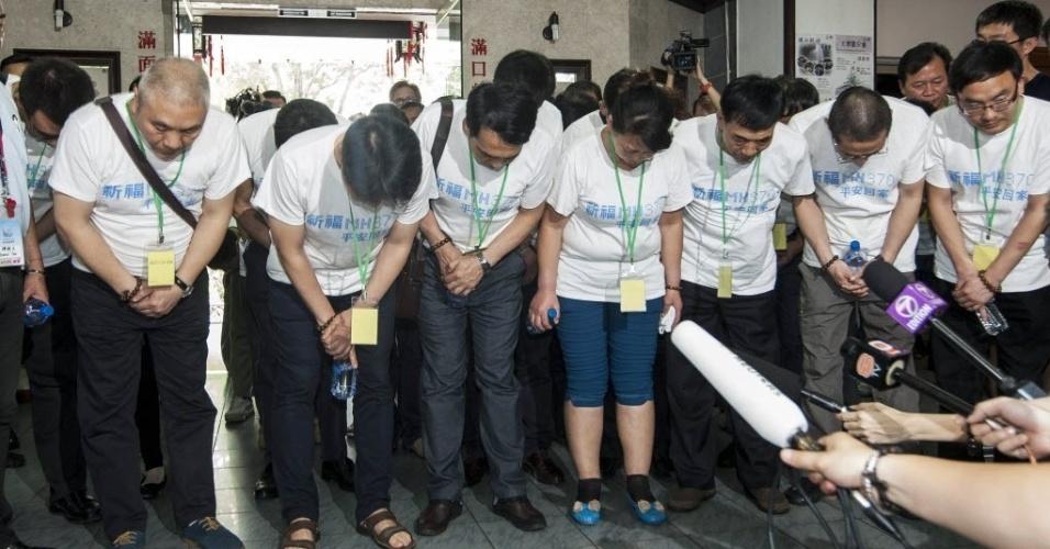 31.mar.2014 - Familiares de passageiros do voo MH370 se inclinam ao realizar orações em templo budista em Petaling Jaya, na Malásia