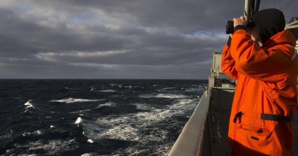 """31.mar.2014 - Foto de 28 de março divulgada nesta segunda-feira (31) mostra técnico da Marinha australiana procurando sinais do avião da Malaysia Airlines desaparecido no dia 8 de março passado. O primeiro-ministro da Austrália, Tony Abbott, declarou nesta segunda-feira (31) que """"nenhum limite de tempo será imposto para a busca do voo MH370, porque o mundo merece saber o que aconteceu"""""""