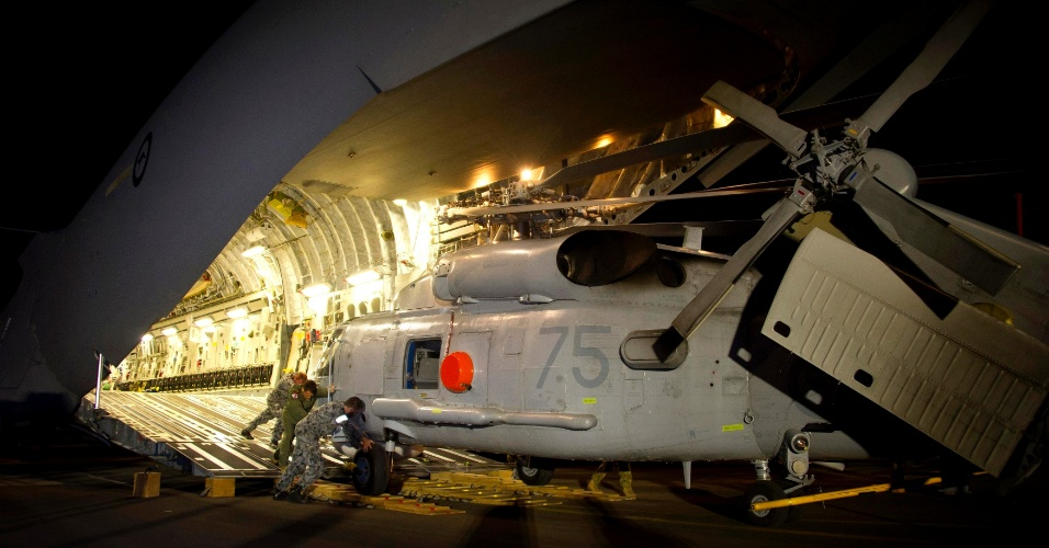 """1º.abr.2014 - Helicóptero da Marinha australiana, que será utilizado nas operações de busca ao avião desaparecido da Malaysian Airlines, é descarregado de avião ao norte de Perth, nesta terça-feira (1º). Segundo a autoridade de aviação civil da Malásia, as últimas palavras ditas por um dos pilotos do voo MH370 para a torre de controle foram """"Boa noite, Malaysian três sete zero"""", mudando o relato anterior de que a mensagem fora um despreocupado """"Tudo bem, boa noite?. Não há sinais dos destroços do avião"""