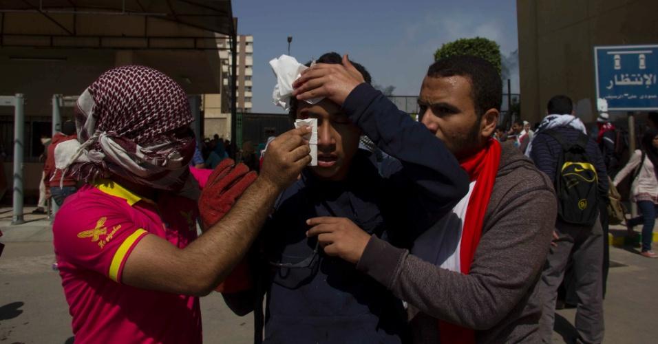 1ºabr.2014 - Um manifestante recebe ajuda de seus companheiros na Universidade de Ain Shams, no Cairo, no Egito, nesta terça-feira (1º). Estudantes e forças de segurança se enfrentaram no campus da universidade hoje