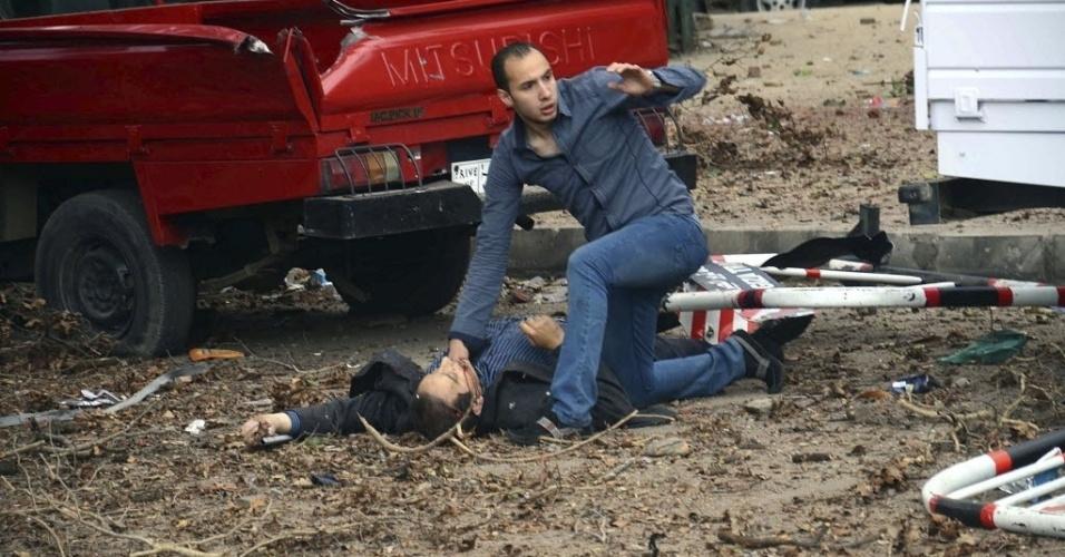 2.abr.2014 - Homem ajuda ferido após um ataque com duas bombas caseiras em um posto policial localizado ao lado da Universidade do Cairo, Egito. Um policial morreu