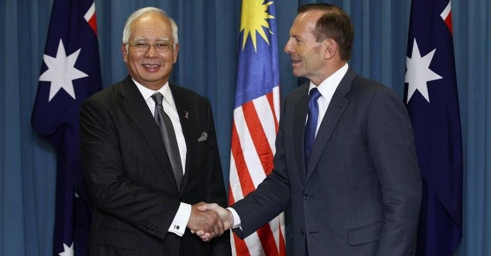3.abr.2014 - Primeiro-ministro malaio Najib Razak (à esq.) e primeiro-ministro australiano Tony Abbott (à dir.) dão um aperto de mãos antes do início de suas negociações sobre a busca do avião desaparecido da Malaysia Airlines, na Área Real da Força Aérea Australiana, localizada perto de Perth