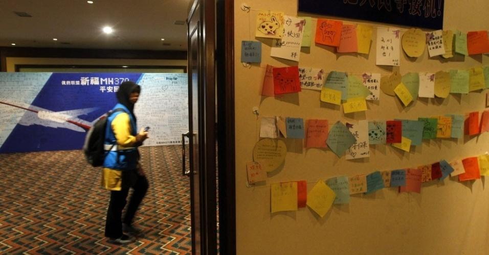 3.abr.2014 - Um homem passa próximo a homenagem aos passageiros desaparecidos no vôo MH370 enquanto o representante da Malaysia Airlines atende a uma conferência de imprensa com os parentes dos passageiros, em um hotel em Pequim, na China