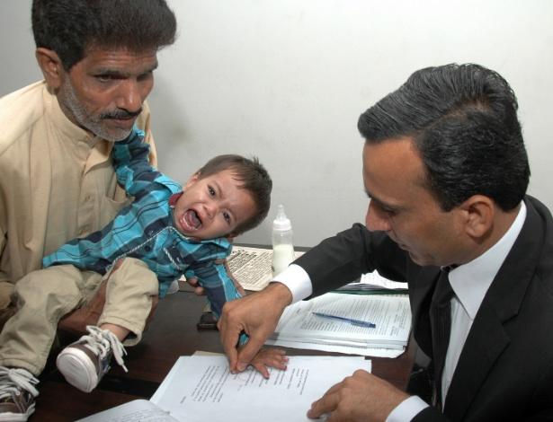 5.abr.2014 - Foto tirada em 3 de abril mostra um policial paquistanês pegando as digitais do bebê Mohammad Musa, que tem nove meses de vida. Ele foi acusado de tentativa de assassinato durante uma operação da polícia