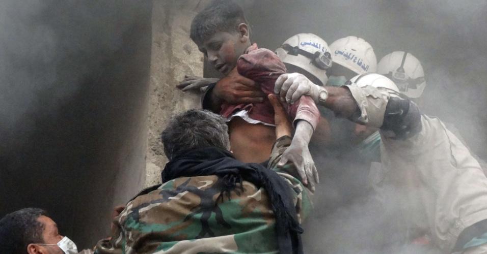 6.abr.2014 - Equipes de emergência retiram sírio de edifício residencial atingido por barril com explosivos, que teria caído de um helicóptero do Exército, neste domingo (6), em Aleppo, na Síria. Mais de 150 mil pessoas já morreram em três anos, por causa da guerra civil no país