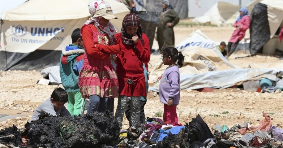 6.abr.2014 - Refugiados sírios observam seus pertences queimados após confronto com forças de segurança no campo de refugiados de Al-Zaatari, em Mafraq, próximo à fronteira entre a Jordãnia e Síria, neste domingo (6). Pelo menos um refugiado sírio foi morto durante o combate