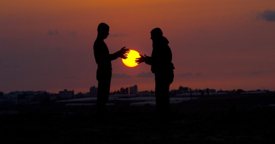 9.abr.2014 - Jovens palestinos brincam com o sol que se põe em Beit Hanun, ao norte da faixa de Gaza