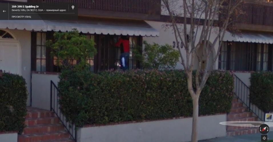 Na Califórnia (EUA), um homem é visto pendurado na janela de uma casa