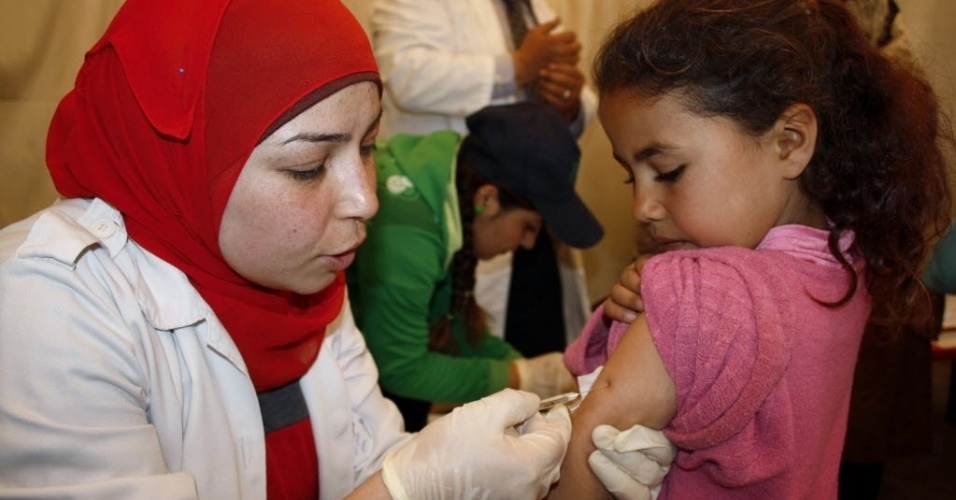 11.abr.2014 - Crianças refugiadas sírias recebem vacina contra a Poliomielite em um campo de refugiados perto da aldeia libanesa de Zahle, no vale de Bekaa