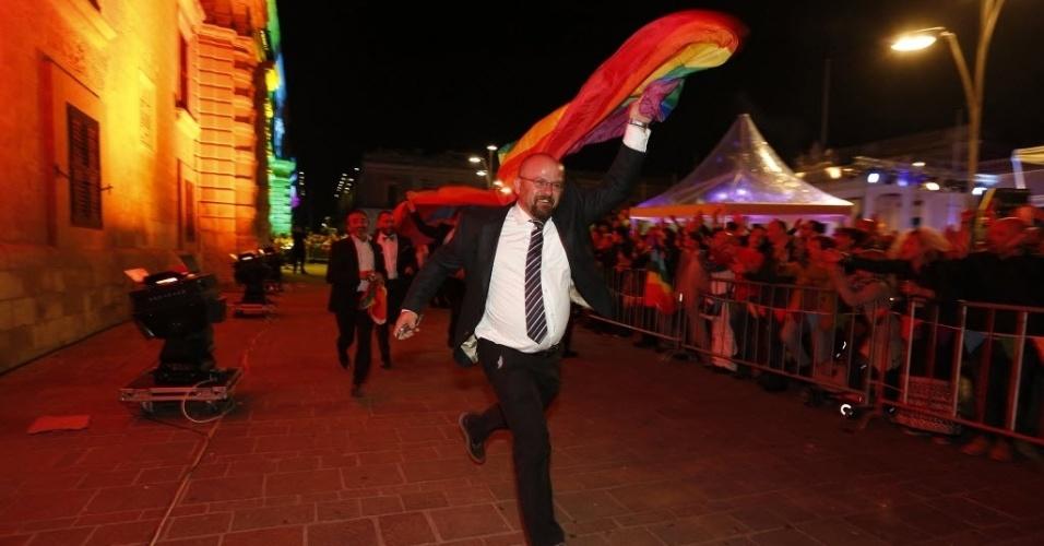 14.abr.2014 - Ativistas dos direitos gays comemora e corre com uma bandeiras do arco-íris em suas mãos, nesta segunda-feira (14), quando o parlamento maltês aprovou uma lei que reconhece parcerias do mesmo sexo em pé de igualdade jurídica com o casamento de pessoas de sexos diferentes, inclusive permitindo casais homossexuais a adotar