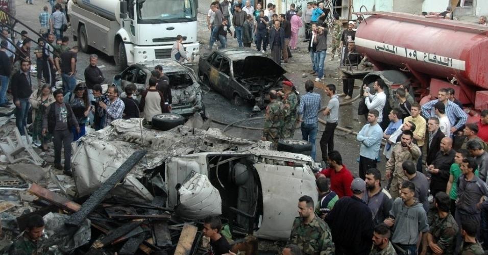 14.abr.2014 - Equipes dos serviços de segurança e de emergência trabalham no local da explosão de um carro-bomba em Homs, na Síria. Segundo o Observatório Sírio para Direitos Humanos, o ataque deixou pelo menos 21 mortos